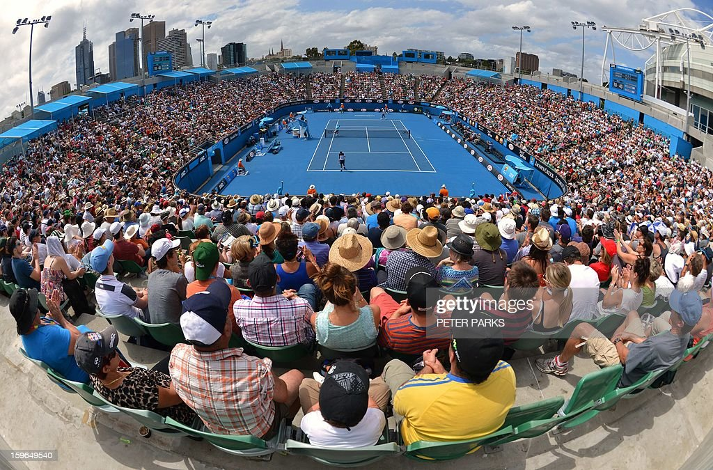 Fans watch as Serbia's Janko Tipsarevic (lower ) takes on France's Julien Benneteau during their men's singles match on day five of the Australian Open tennis tournament in Melbourne on January 18, 2013.