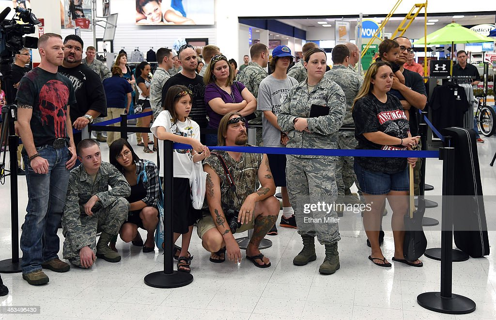 Fans watch Five Finger Death Punch's new video as it is shown at Nellis Air Force Base as the band highlights its campaign to raise awareness about veterans suffering from post-traumatic stress disorder (PTSD), in part by launching the video 'Wrong Side of Heaven,' that deals with the subject on August 11, 2014 in Las Vegas, Nevada.