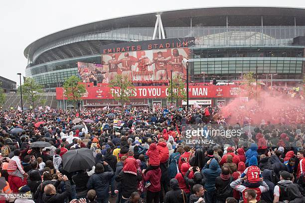 Fans watch in the rain as Arsenal players celebrate with the trophy outside the Emirates Stadium during the Arsenal victory parade in London on May...