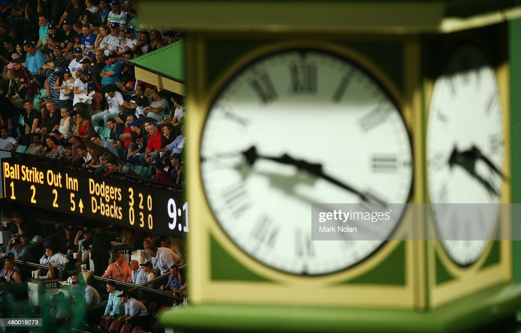 Fans watch on as a score board is pictured in the background of the SCG members stand clock during the opening match of the MLB season between the Los Angeles Dodgers and the Arizona Diamondbacks at Sydney Cricket Ground on March 22, 2014 in Sydney, Australia.