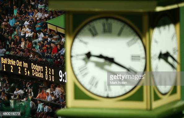 Fans watch on as a score board is pictured in the background of the SCG members stand clock during the opening match of the MLB season between the...