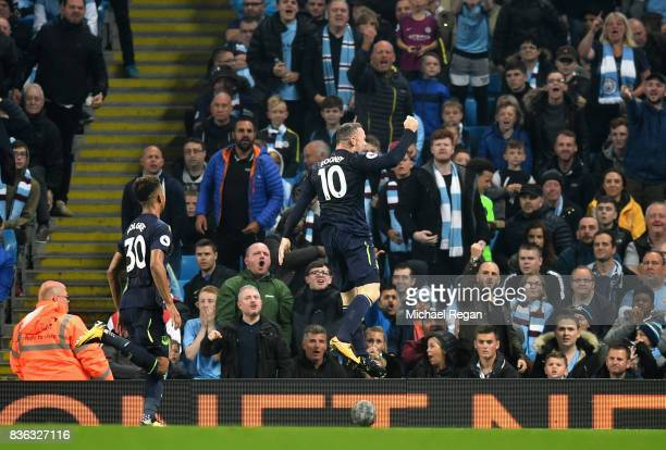 Fans watch on as Wayne Rooney of Everton celebrates after scoring his sides first goal during the Premier League match between Manchester City and...