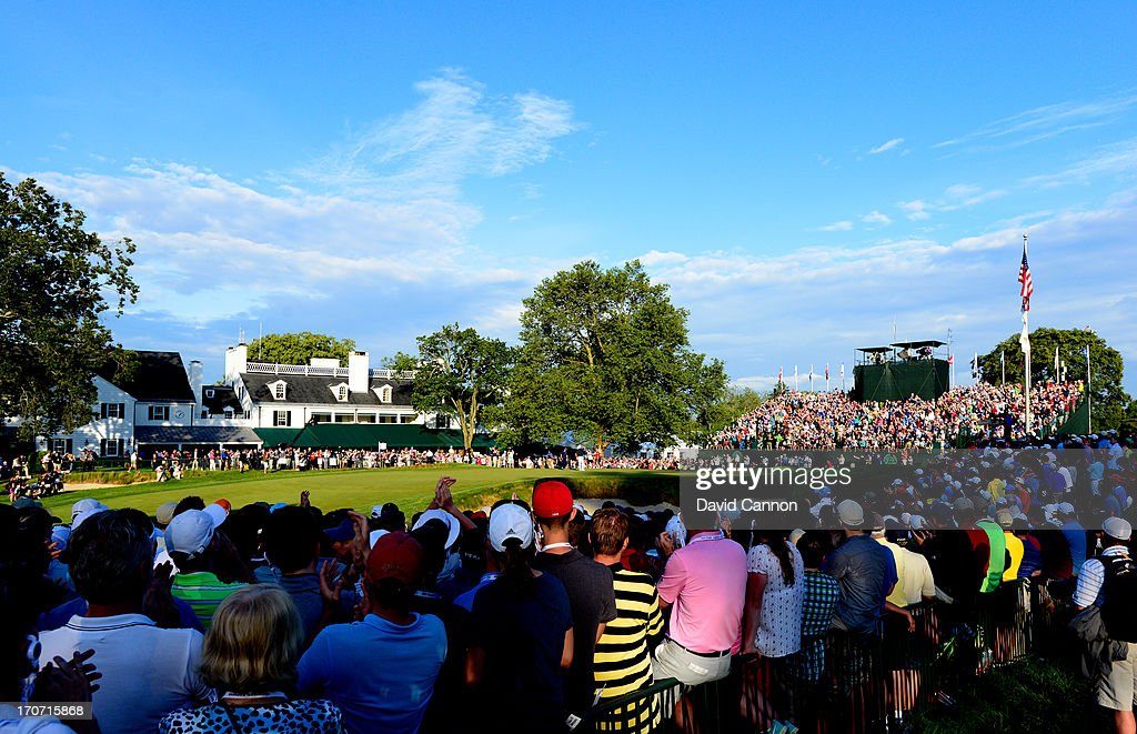 Fans watch play on the 18th green as Justin Rose of England reacts after putting on the 18th hole to complete the final round of the 113th U.S. Open at Merion Golf Club on June 16, 2013 in Ardmore, Pennsylvania.