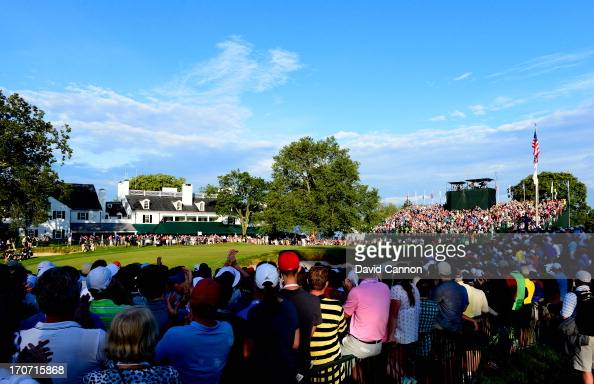 Fans watch play on the 18th green as Justin Rose of England reacts after putting on the 18th hole to complete the final round of the 113th US Open at...