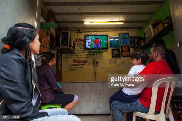 Fans watch the 2014 FIFA World Cup final match between Argentina and Germany match in the neighborhood streets of Favela do Moinho on July 13 2014 in...
