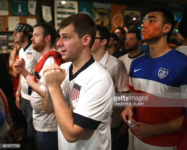 Fans watch the 2014 FIFA World Cup match between Belgium and the USA from Jack Dempsey's Pub in New York on July 1 2014 The US was defeated in extra...