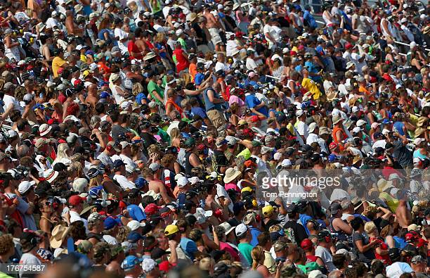 Fans watch the action during the NASCAR Sprint Cup Series 44th Annual Pure Michigan 400 at Michigan International Speedway on August 18 2013 in...
