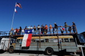 Fans watch the action from the top of a bus in the infield during the NASCAR Nationwide Series O'Reilly Auto Parts 300 at Texas Motor Speedway on...