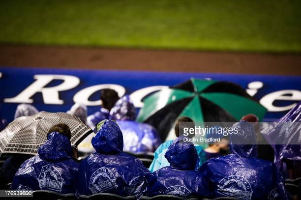 Fans watch the action wearing purple ponchos as rain falls during a game between the Colorado Rockies and the San Diego Padres at Coors Field on...