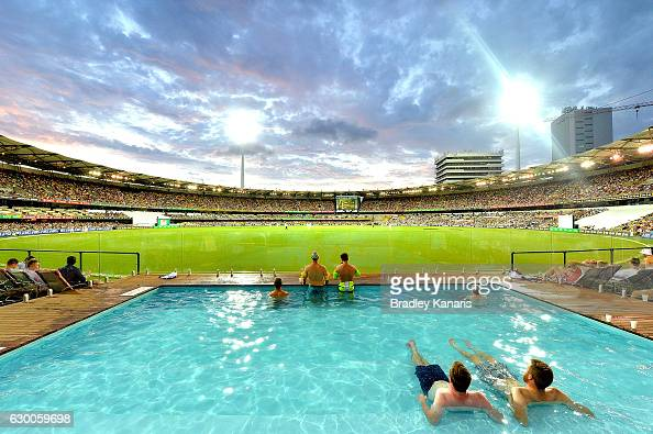 Fans watch the Cricket from the pool as the sun sets during day two of the First Test match between Australia and Pakistan at The Gabba on December...