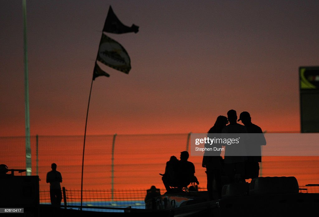 Fans watch the NASCAR Nationwide Series Camping World RV Service 300 at sunset from the top of their RV's in the infield at Auto Club Speedway on...