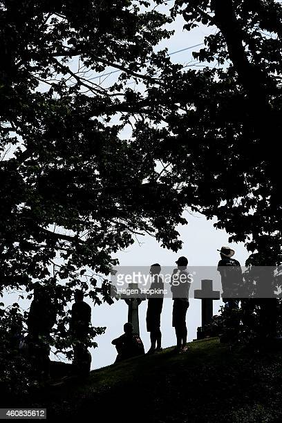 Fans watch the races from Heads Road Cemetery during the Cemetery Circuit Motorcycle Races on December 26 2014 in Wanganui New Zealand