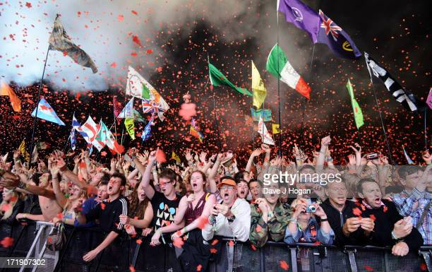 Fans watch the Rolling Stones perform on the Pyramid Stage at day 3 of the 2013 Glastonbury Festival at Worthy Farm on June 29 2013 in Glastonbury...