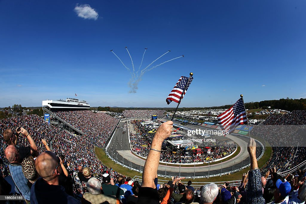 Fans wave American flags as five CJ-6A's from Affordable Warbirds perform a flyover prior to the NASCAR Sprint Cup Series Goody's Headache Relief Shot 500 Powered By Kroger at Martinsville Speedway on October 27, 2013 in Martinsville, Virginia.