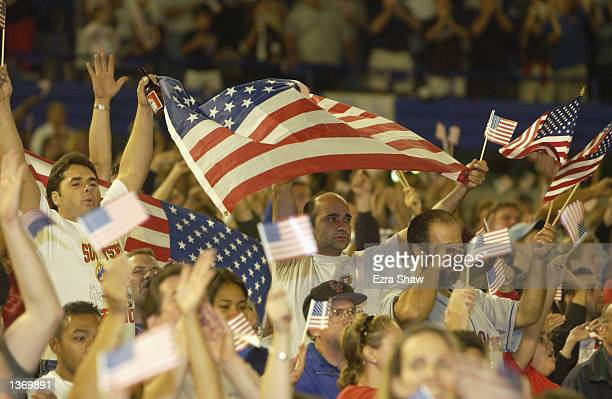 Fans wave American flags while Marc Anthony sings the National Anthem before the New York Mets game against the Atlanta Braves on September 21 2001...