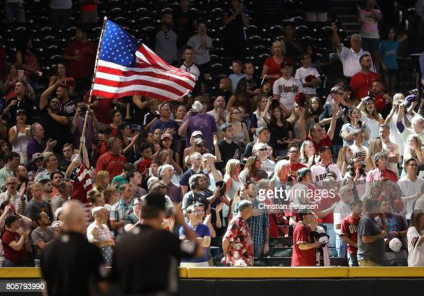 Fans wave an American flag during the singing of 'God Bless America' in the seventh inning of the MLB game between the Arizona Diamondbacks and the...