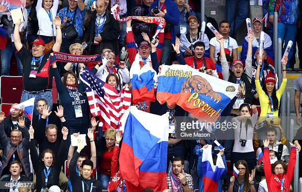 Fans wave flags during the Men's Ice Hockey Preliminary Round Group A game between Russia and the United States on day eight of the Sochi 2014 Winter...