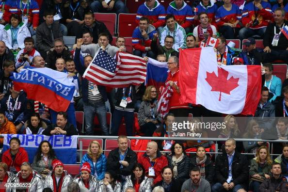 Fans wave flags during the Men's Ice Hockey Semifinal Playoff between Canada and the United States on Day 14 of the 2014 Sochi Winter Olympics at...