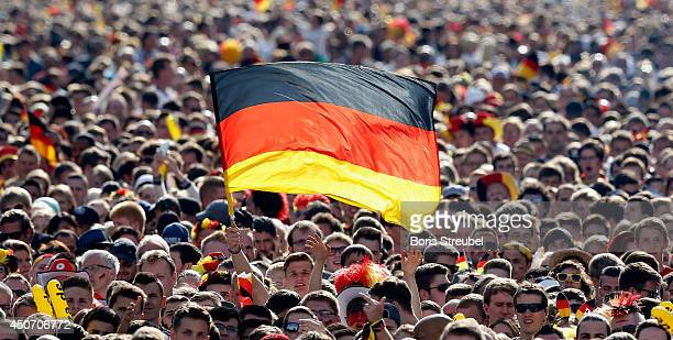 Fans wave German flags at the Fanmeile public viewing at Brandenburg Gate during the 2014 FIFA World Cup Brazil Group G match between Germany and...