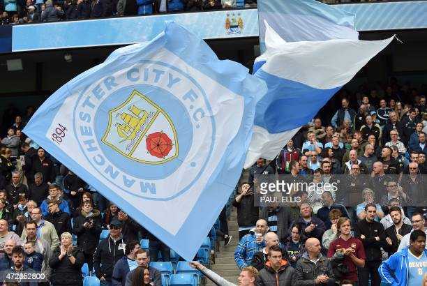 Fans wave Manchester City flags in the stands ahead of the English Premier League football match between Manchester City and Queens Park Rangers at...