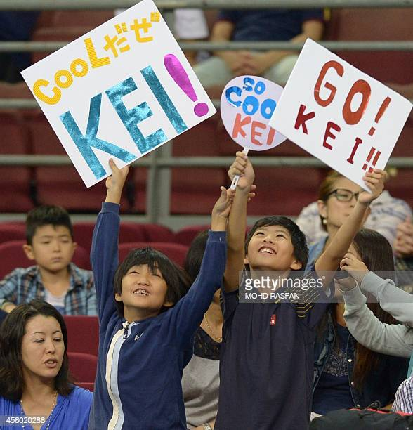 Fans wave placards during a match between Kei Nishikori of Japan and Rajeev Ram of the US in the men's singles second round at the ATP Malaysia Open...