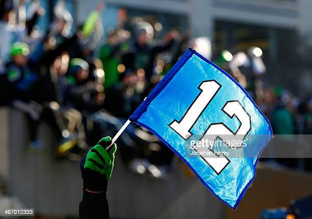 Fans wave the 12th Man flag to celebrate Seattle Seahawks victory in Super Bowl XLVII during a parade on February 5 2014 in Seattle Washington