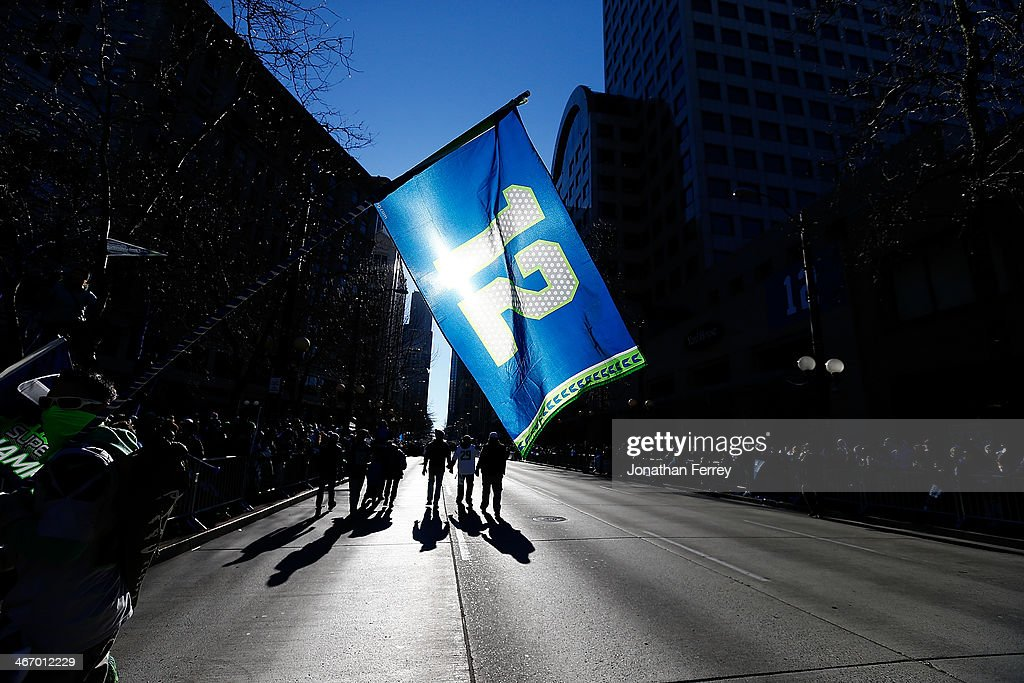 Fans wave the 12th Man flag to celebrate the Seattle Seahawks victory in Super Bowl XLVII during a parade on February 5, 2014 in Seattle, Washington.