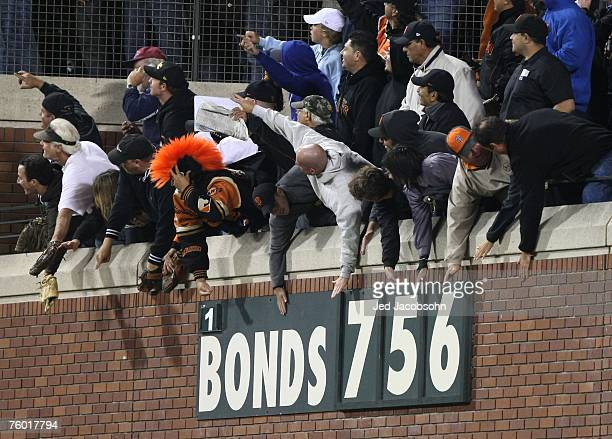 Fans wave to Barry Bonds of the San Francisco Giants after hitting career home run during the Major League Baseball game against the Washington...