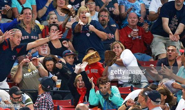 Fans wear many different looks as a first inning foul ball heads their way The Boston Red Sox hosted the Baltimore Orioles in an MLB regular season...
