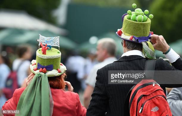 Fans wear tennisthemed hats as they walk through The All England Lawn Tennis Club in Wimbledon southwest London on July 4 2017 on the second day of...