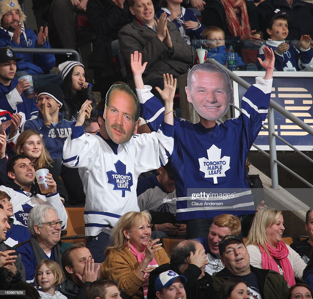 Fans wearing alumni masks featuring Johnny Bower and Wendel Clark stand and cheer during a game between the Winnipeg Jets and the Toronto Maple Leafs on March 16, 2013 at the Air Canada Centre in Toronto, Ontario, Canada. The Jets defeated the Leafs 5-4 in an overtime shootout.