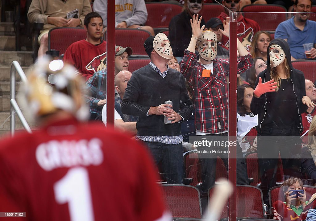 Fans wearing hockey masks for Halloween cheer during a break from the NHL game between the Phoenix Coyotes and the Nashville Predators at Jobing.com Arena on October 31, 2013 in Glendale, Arizona. The Coyotes defeated the Predators 5-4 in an overtime shoot out.
