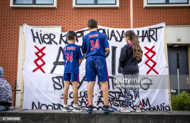 Fans wearing shirts with the number 34 of Ajax midfielder Abdelhak Nouri stand in front of a banner reading 'Here beats a Ajax heart Stay Strong...