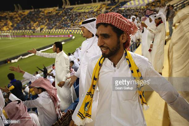 Fans wearing traditional local dress react to play during the Gharafa vs Kharaitiyat Qatar Stars League football match at Al Gharafa Stadium on...