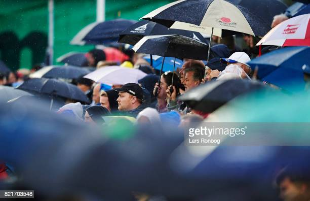 Fans with umbrellas in the rain during the Danish Alka Superliga match between FC Helsingor and OB Odense at Helsingor Stadion on July 24 2017 in...