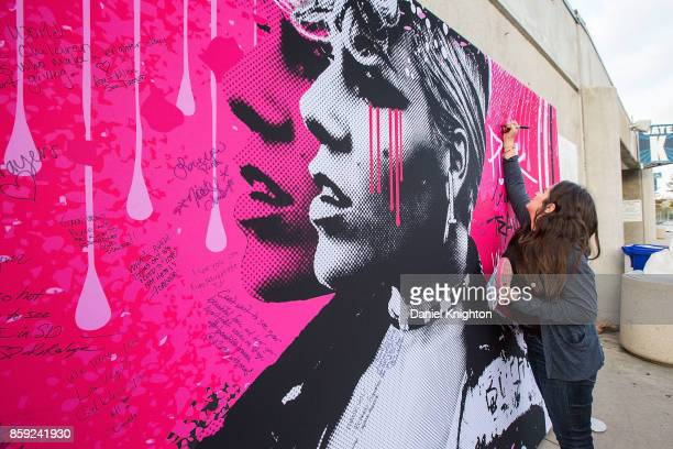Fans write notes on a billboard advertising an upcoming show by Pnk at SDCCU Stadium on October 8 2017 in San Diego California