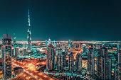 Fantastic nighttime Dubai skyline with illuminated skyscrapers. Rooftop perspective of downtown Dubai, UAE.