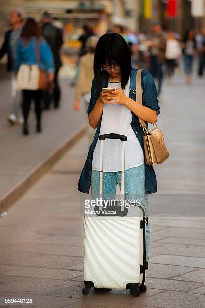 A far eastern looking woman a white trolley beside her stops in Corso Vittorio Emanuele in Milano to watch her smartphone