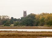 far off church top spire overcast river coast; essex; england; uk