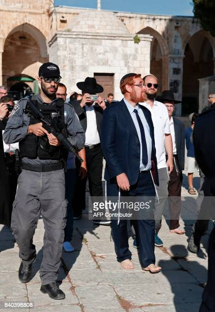 Far right Israeli Rabbi and Israeli parliament member Yehuda Glick walks barefoot escorted by Israeli police and supporters inside the flashpoint...