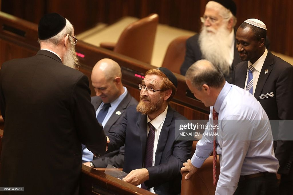 Far right Israeli rabbi Yehuda Glick (C) takes his seat during a Knesset session after he was sworn in, on May 25, 2016, in Jerusalem. The resignation of Israeli Defence Minister Moshe Yaalon last week has opened the way for the American-born Yehuda Glick hardliner who advocates Jewish prayer at the Al-Aqsa mosque compound to enter parliament. / AFP / MENAHEM