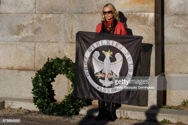 A far right wing supporter holds a Polish flag as she poses for a picture next to a Laurel wreath at the end of the 'Crown March' outside the Valley...