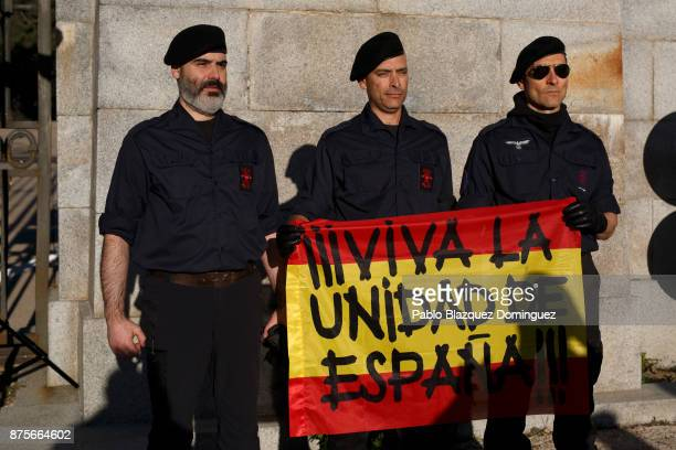 Far right wing supporters pose for a picture as they hold a Spanish flag reading 'For the unity of Spain' at the end of the 'Crown March' outside the...
