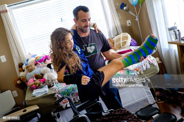 Faran Kaplan picks up his daugher Sophia to place her in her wheelchair in their home on Wednesday September 27 2017 in Ashburn Virginia Faran's wife...