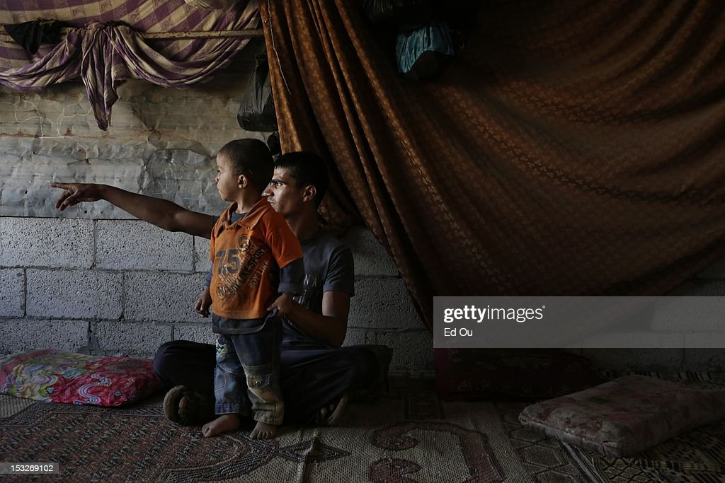 Fares Abu Rajn, 19, plays with a relative in his makeshift home in Gaza's Forgotten Neighborhood on Sept. 6, 2012. A United Nations report issued last week questioned whether Gaza will be 'a liveable place' in 2020, citing shortages of food, clean water, electricity, jobs, hospital beds and classrooms amid an exploding population in what is already one of the most densely populated patches of Earth. The Forgotten Neighborhood, where about 40 families totalling 200 people have settled over the past four years near a municipal slaughterhouse in southern Gaza City, is an extreme case: the nicer homes are made of cinder blocks, or even stone slabs left from the security wall before Israel's disengagement, while others live in tents of rusty zinc sheets with branches for roofs.
