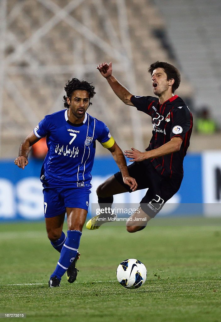 Farhad Majedi of Esteghlal and <a gi-track='captionPersonalityLinkClicked' href=/galleries/search?phrase=Alvaro+Fernandez&family=editorial&specificpeople=2946918 ng-click='$event.stopPropagation()'>Alvaro Fernandez</a> of Al Rayyan in action during the AFC Champions League Group D match between Esteghlal and Al Rayyan at Azadi Stadium on April 23, 2013 in Tehran, Iran.