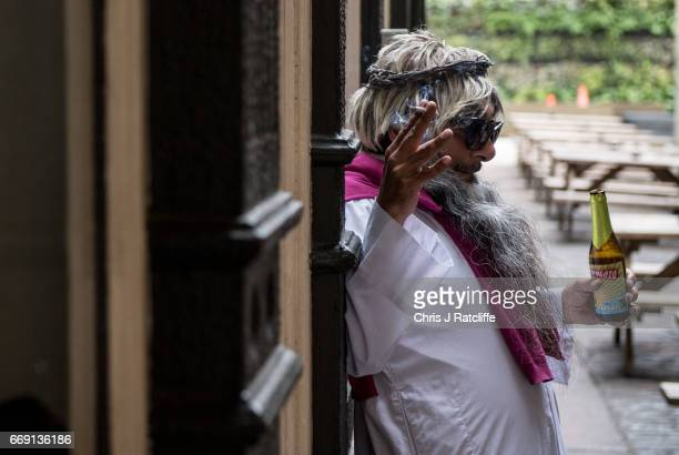 Farhan Rasheed leans against a wall smokes a cigarette and drinks a beer dressed as Jesus outside the Christopher Inn during the Christathon X pub...