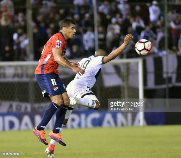 Farid Diaz of Paraguays Olimpia vies for the ball with Carlos Bonet of Paraguay's Nacional during their 2017 Copa Sudamericana football match at...