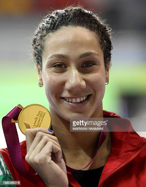 Farida Osman of Egypt poses on the podium with her gold medal after winning the women's 50m backstroke event during the 2011 Arab Games in the Qatari...