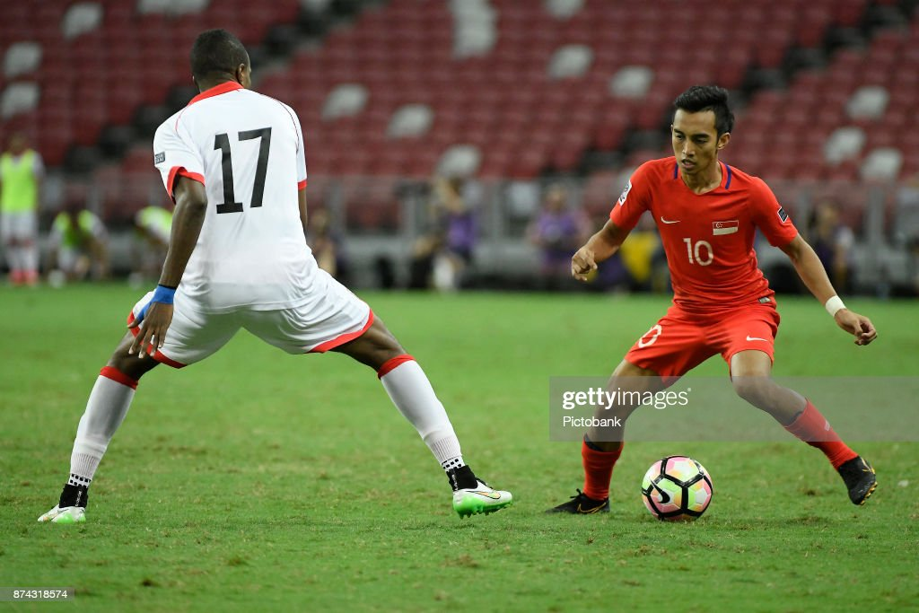 Faris Ramli of Singapore (R) runs with the ball against Abubaker Aadem of Bahrain (L) during the Asian Cup Qualifier match between Singapore and Bahrain at the Singapore Sports Hub on November 14, 2017, in Singapore, Singapore.